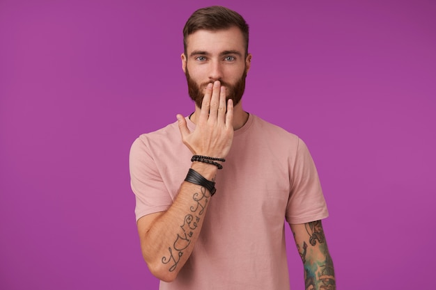 Affascinante giovane uomo tatuato dagli occhi azzurri con tatuaggi che indossa una maglietta beige e accessori alla moda mentre posa sul viola, tenendo il palmo sulla bocca e guardando positivamente