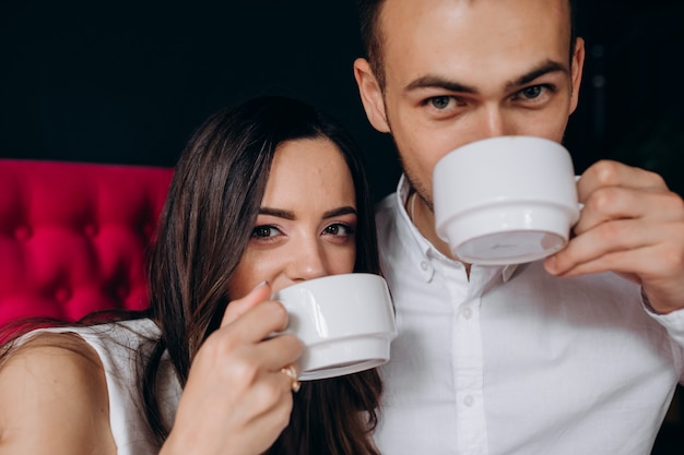 Charming young wedding couple drinks coffee sitting on a bright pink couch
