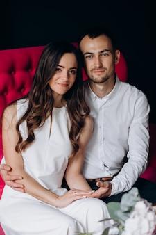 Очаровательная молодая свадебная пара сидит на ярко-розовый диван в кафе
