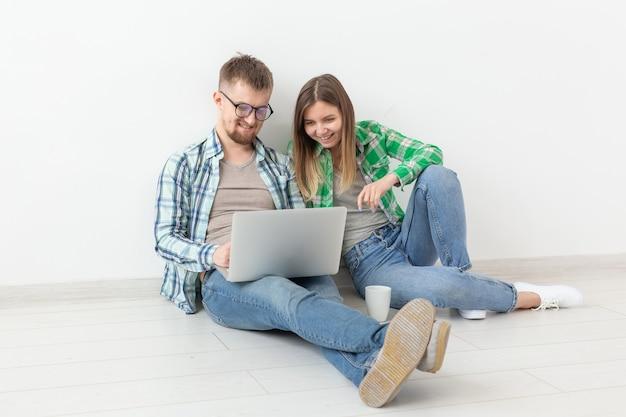 Очаровательная молодая женщина и улыбающийся мужчина смотрят интернет-магазины, используя ноутбук, чтобы купить сантехнику в