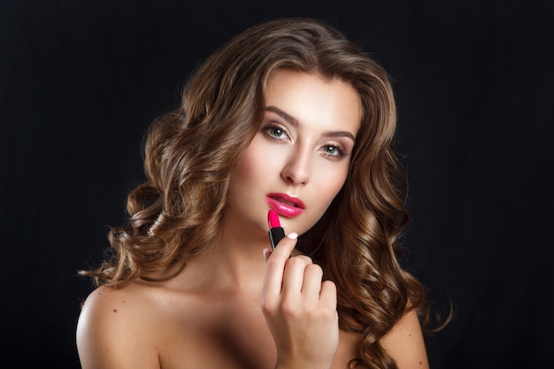 Charming young woman applying red lipstick. photo of beautiful woman with perfect skin