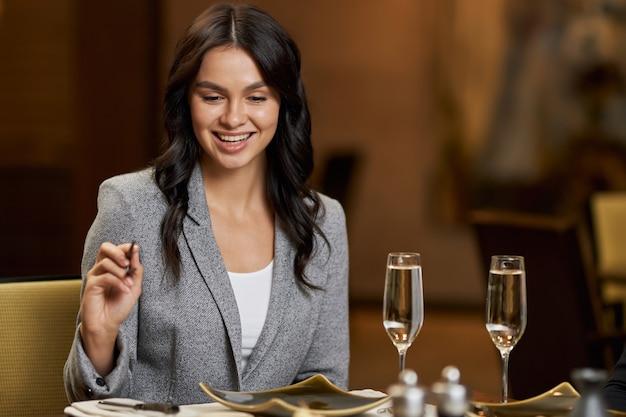 箸で食べる準備ができている魅力的な若い女性