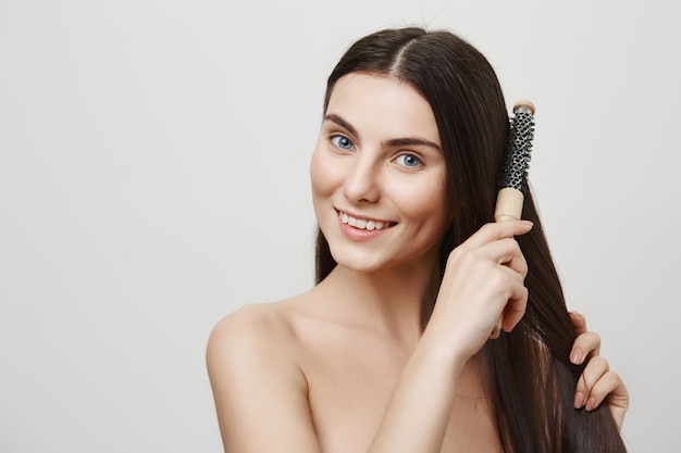 Charming young woman brushing hair and smiling