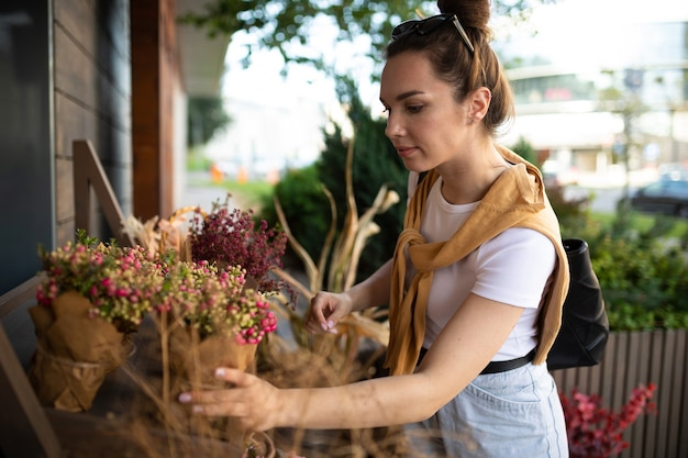 Charming young woman buying flowers at garden summer shop.