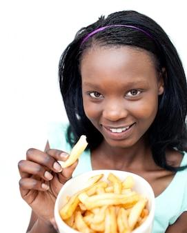 Очаровательная молодая женщина есть картофель фри
