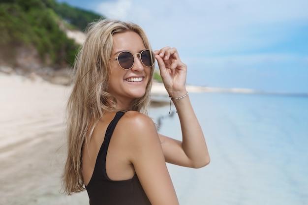 맑은 모래 해변에서 여름 휴가를 즐기는 매력적인 젊은 여자