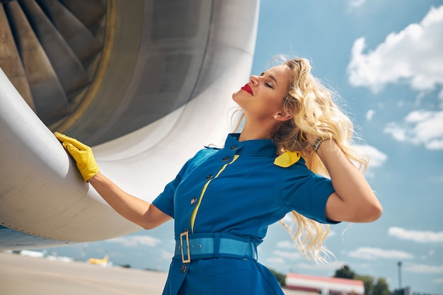 Charming young woman flight attendant touching her hair and smiling while placing hand on plane engine
