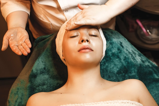 Очаровательная молодая женщина, имеющая массаж лица с гиалуроновой кислотой в оздоровительном спа-центре.