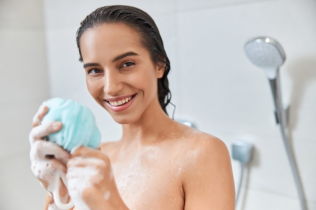 Charming young woman holding exfoliating loofah sponge
