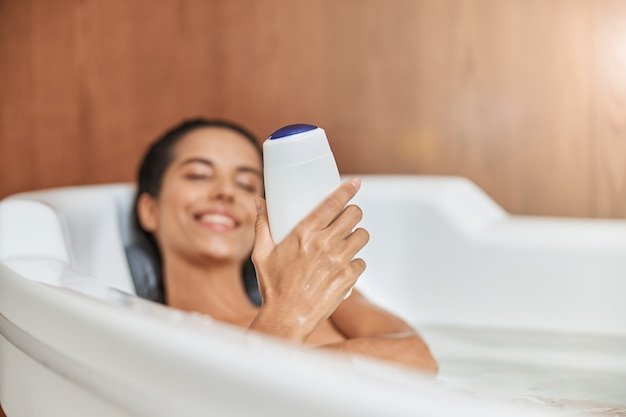 Charming young woman holding shower gel while taking bath