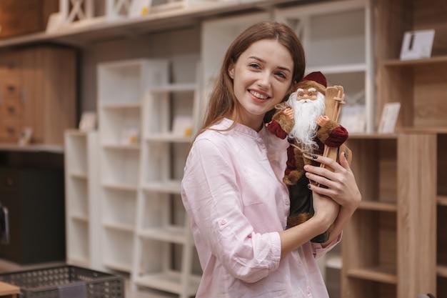 Charming young woman hugging toy santa claus, enjoying shopping for x-mas decor