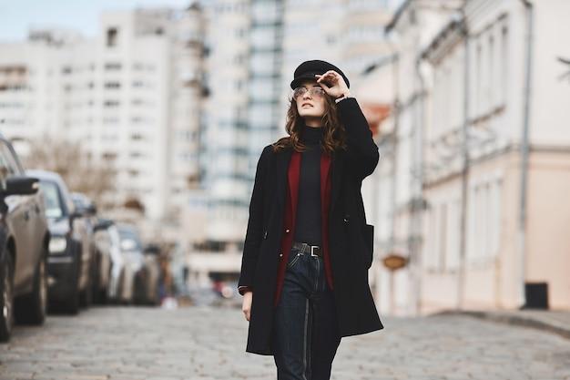 겨울 코트, 유행 모자, 선글라스를 입은 매력적인 젊은 여성이 대도시의 거리를 걷고 있습니다. 스트리트 패션의 개념. 텍스트, 복사 공간을위한 장소.