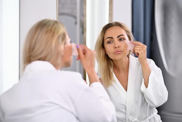 목욕 가운을 입은 매력적인 젊은 여성이 거울에 비친 자신의 모습을 바라보는 gua sha 석재 마사지기로 림프 배수 얼굴 마사지를 하고 있습니다.