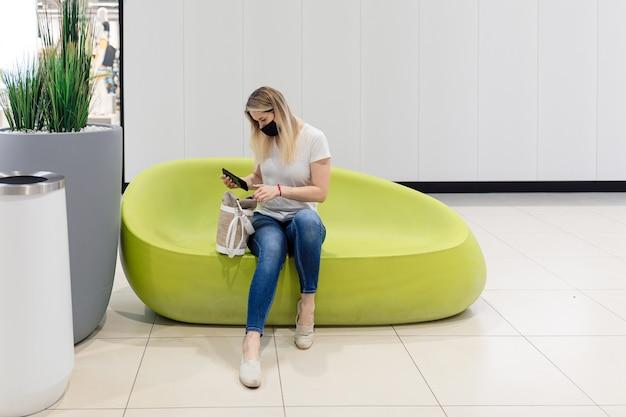 黒いマスクの魅力的な若い女性は、ショッピングセンターのモダンなソファに座っている間、彼女の携帯電話をバッグから取り出します。現代のテクノロジー。個人用保護具。ショッピングと楽しみ。