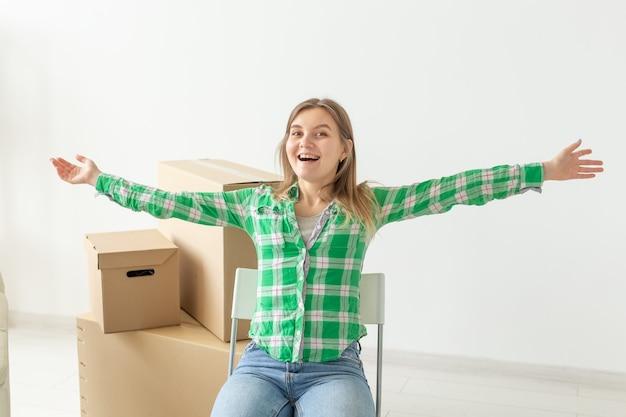 캐주얼 한 옷을 입은 매력적인 젊은 여성이 이사하는 동안 새 아파트 거실에있는 물건 상자 사이의 의자에 앉아 기뻐합니다. 새로운 주택과 집들이의 개념. copyspace