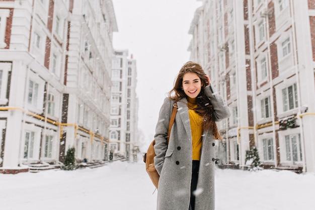 大都市で降雪を楽しんでいる長いブルネットの髪を持つコートの魅力的な若い女性。陽気な感情、笑顔、クリスマス気分、前向きな顔の感情、冬の天気。テキストのための場所。