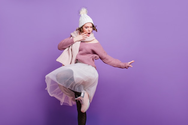 Очаровательная молодая женщина в смешной шляпе эмоционально позирует на фиолетовой стене. домашнее фото очаровательной девушки-модели в пышной белой юбке и зимних аксессуарах.