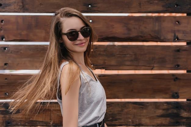 木製の壁に手を振って髪でポーズをとってメガネの魅力的な若い女性。幸せな笑顔で踊る喜んでいる白人の女の子の屋外ショット。
