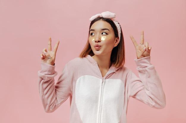 잠옷을 입은 매력적인 젊은 여성이 휘파람을 불고 분홍색 외진 벽에 평화 표지판을 보여줍니다