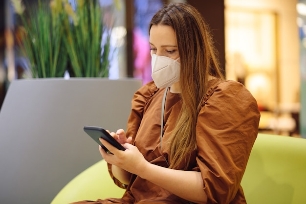 ショッピングセンターの個人用保護マスクを着用した魅力的な若い女性が電話でショッピングリストをチェック