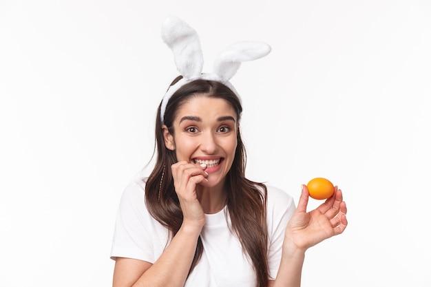 Очаровательная молодая женщина в кроличьих ушах держит цветное яйцо