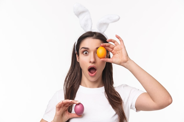 着色された卵を保持しているウサギの耳の魅力的な若い女性