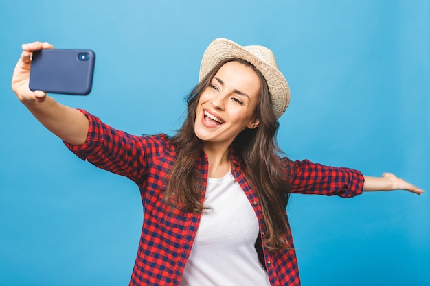 白い帽子をかぶった魅力的な若い女性が旅行して自分撮りをします