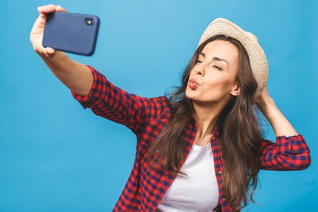 白い帽子の旅行で魅力的な若い女性は自分撮りを取ります