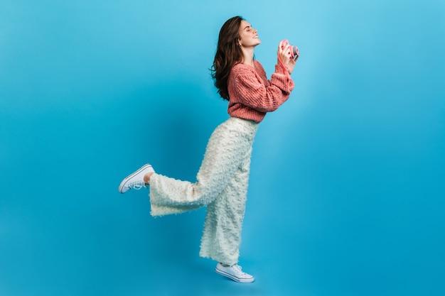 白いズボンの魅力的な若い女性はピンクのカメラで写真を作ります。ピンクのセーターのブルネットのフルレングスの肖像画。