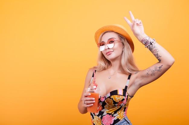 スタジオで黄色の背景の上にサングラスと新鮮なオレンジジュースを飲みながら平和の兆候を作る魅力的な若い女性