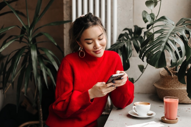 Charming young woman in massive earrings and bright sweater chats in phone while sitting in cafe over cup of coffee