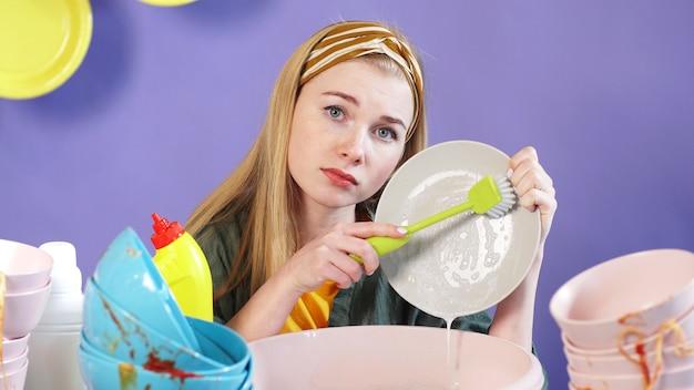 孤立した背景と汚れた皿の山に魅力的な若い女性