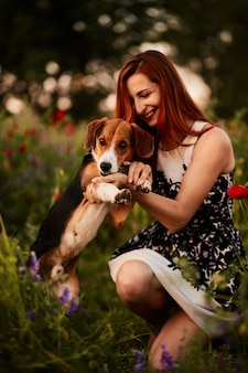 Charming young woman plays with a beagle on a green field