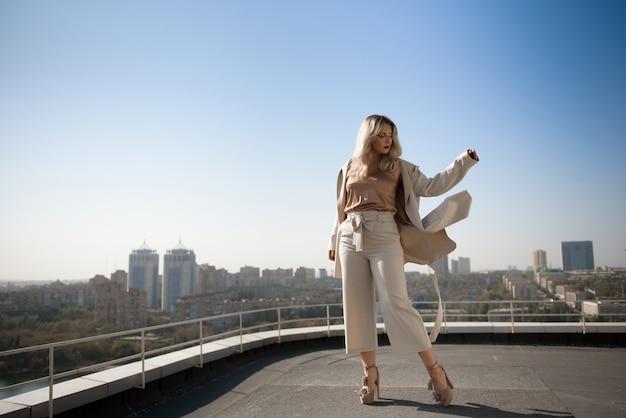 町を眺めながらホテルの屋上でポーズをとる魅力的な若い女性。