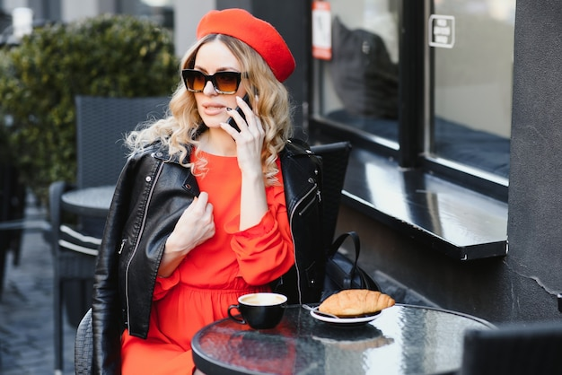 Charming young woman in red dress and stylish beret puts on eyeglasses and smiles