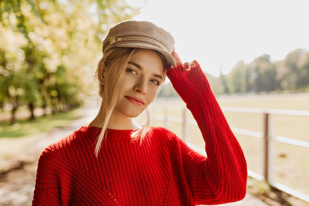 Charming young woman in red pullover and light hat looking good in the park. beautiful blonde wearing nice accessories and trendy clothes in the autumn.