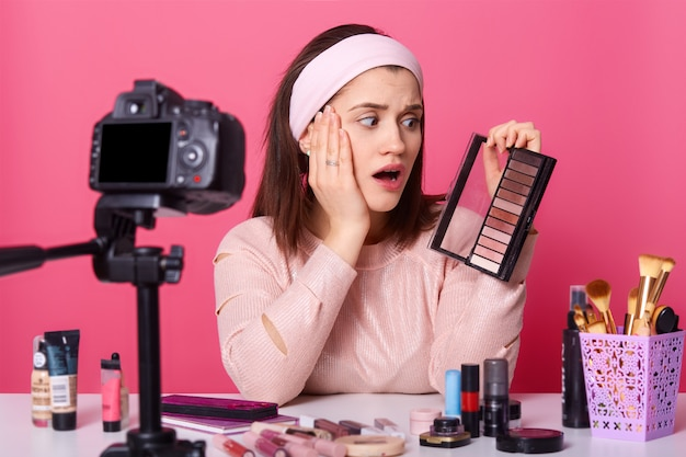 Charming young woman sits in front of camera, has surprised expression, surrounded with beauty products