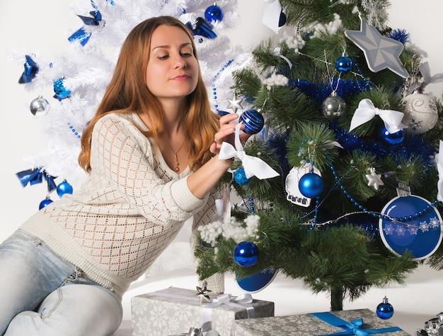 魅力的な若い女性がクリスマスツリーの近くに座って、次の休日を楽しんでいます