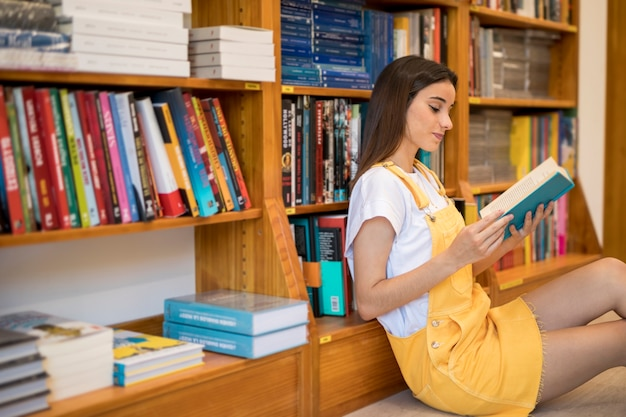 Charming young woman sitting in library and reading book