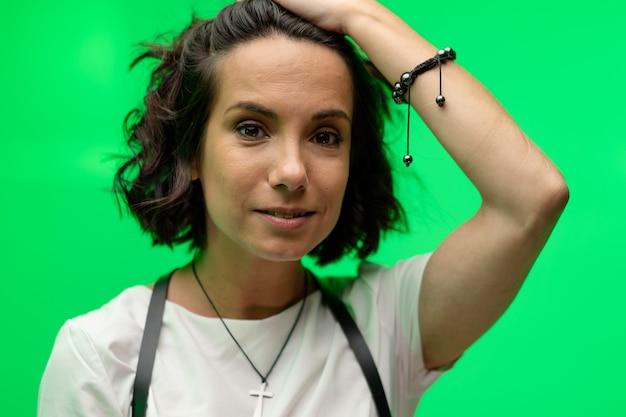 魅力的な若い女性は、緑の背景にポーズをとって彼女の髪を真っすぐにします。クロマキーの女性の肖像画。