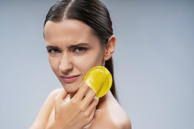 Очаровательная молодая женщина, использующая отшелушивающую губку для чистки