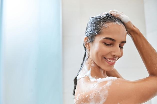 Очаровательная молодая женщина, моющая волосы в душе