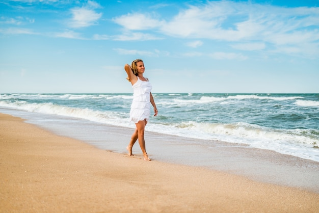 Charming young woman in a white dress walks along the calm sea waves on the sandy coast against a surface of blue sky