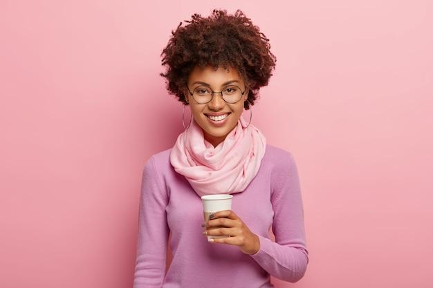 Очаровательная молодая женщина с афро-прической пьет кофе на вынос из одноразовой чашки