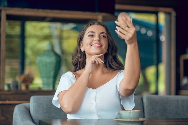 鏡で自分を賞賛する茶色の目と白い歯の笑顔を持つ魅力的な若い女性