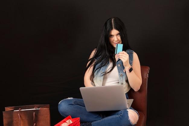 Очаровательная молодая женщина с кредитной картой, использующая ноутбук для покупок в интернете, изолированная на черной поверхности