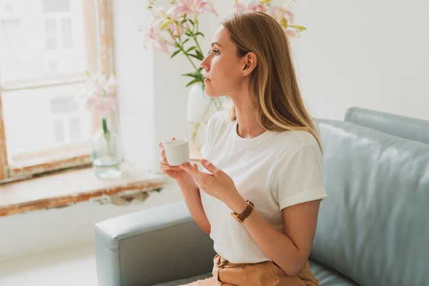 Charming young woman with a cup of coffee sitting on the sofa at home