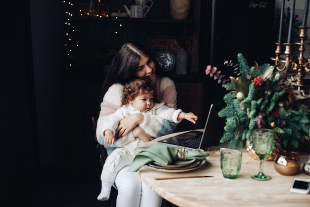 Charming young woman with cute kid sitting at table and looking at laptop screen