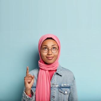 Affascinante giovane donna con la pelle scura e sana, guarda e punta verso l'alto, indica con il dito indice, indossa l'hijab rosa, giacca alla moda, si trova sopra il muro blu, pubblicizza lo spazio della copia, mostra la strada giusta