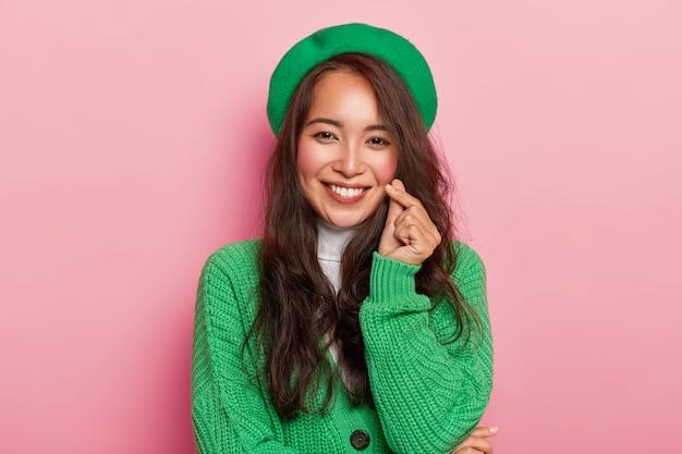 Affascinante giovane donna con i capelli lunghi scuri fa segno di amore coreano, forma il cuore con le dita, indossa berretto verde alla moda brillante e maglione sui pulsanti
